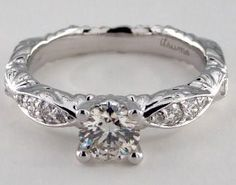 The intricate details are what make this ring amazing. This very unique engagement ring has a decorated band with a carved design and a very unique pave setting. On each side, four pave diamonds, cascading in size, are embedded together, then a single pave diamond sits lower on the band. This ring can be set with a round or princess cut diamond.