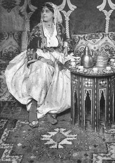 Algerian Woman wearing an Embroidered Jacket and a large pants/skirt, that is constructed like a skirt  but, closed at the bottom leaving two openings at each end of the hem for the legs, she is having an attractive head scarf on her head , held n place by a headband, and as is customary in north African society, she is bedecked in jewelry, and her slippers are embroidered.