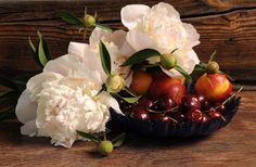 White Petaled Flower on Brown Basket Beside Grapes  Free Stock Photo