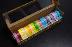 Here's a splendid piece of recycling from Melissa at To Boldly Fold. She took an empty plastic wrap box (and the tube that the wrap came on), and modified them into a handy way to store her collection of Japanese masking tapes.