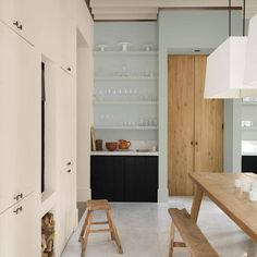 dark wood and pale blue kitchen with open shelving and large wooden table