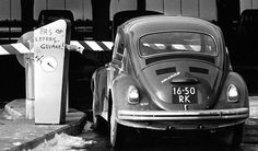 VW Beetle at the closed gate of a garage in the Amsterdam suburb of Bijlmer. Amsterdam, The Netherlands, February 1, 1972