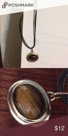 Brown and silver pendant. Choker with black cord Beautiful brown stone in silver case. Triple black cords up to clasp. Could be Tiger Eye not sure Jewelry Necklaces