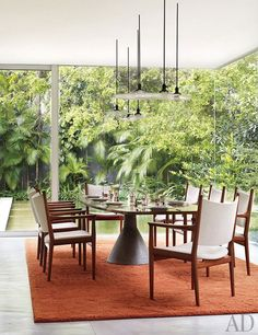 The dining room, with vintage pendant lights, a Jorge Zalszupin table, and Hans J. Wegner chairs.