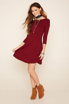 A ribbed knit dress with 3/4 sleeves, a boat neckline, and a plunging lace-up back.