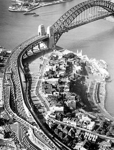 The morning peak commute on the Sydney Harbour Bridge approaches in 1966. Note the constricting effect of merging traffic in the left centre and the Sydney Opera House under construction top left.