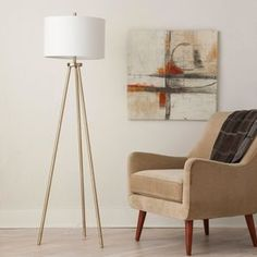 Give artistic appeal to your home with this Tripod Floor Lamp from Project 62™. The base, built from slim brass posts, connects to shining hardware for a graceful, mid-century modern furniture look all capped off with a simple white drum shade. This look pairs with a wide variety of furniture styles for a versatile lighting option you'll love.<br><br>1962 was a big year. Modernist design hit its peak and moved into homes across the country. And in Minnesota, Target wa...