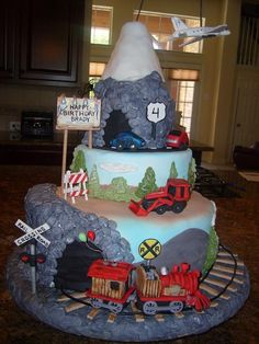 chocolate cake with ganache filling covered in fondant.  train, airplane, cars and bulldozer made of fondant.  debris is chopped jelly bellies.  the track is twizzler airbrushed in black.   a little motor in the top tier spun the airplane around.  all the kids loved it!