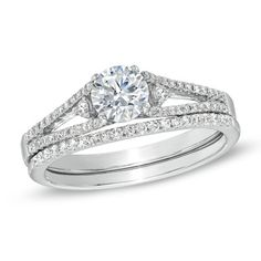 Fashioned in 14K white gold, the engagement ring showcases a 1/2 CT. round diamond center stone flanked by two smaller diamonds