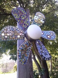 Repurposed Ceiling Fan Flower with Mosaic Tile. Even spins in the wind. = How often have I seen cheap ceiling fans in Salvation Army. Buying them next time.
