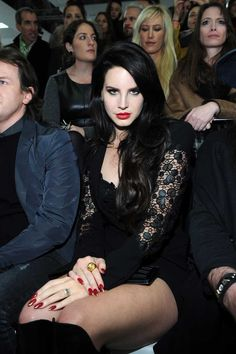 """Lana del Rey wearing a black jacket enriched by lace on the sleeves that matched the shorts and the top. She completed her look with a pair of """"signature"""" black boots, and a black clutch - all from the Versace Spring 2013 collection"""