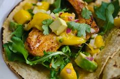 For the fish tacos    1 teaspoon smoked paprika  1/2 teaspoon ground cumin  3/4 teaspoon salt, divided  1/4 teaspoon freshly ground black pepper  1 pound firm white fish such as halibut or tilapia  1 tablespoon canola oil  8 corn tortillas  For the salsa:    1/2 chopped peeled ripe mango  1 avocado sliced and peeled   1/4 cup finely chopped red onion  1/2 jalapeño pepper finely chopped  2 tablespoons finely chopped fresh cilantro  1 tablespoon freshly squeezed lime juice
