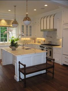 Loving the barrel range hood with forged iron straps, marble subway tiled backsplash and Thomas O'Brien Hicks pendants in this kitchen...not to mention the size of the island!