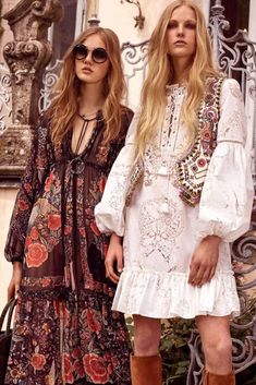 a pair of models, wearing a brown maxi dress, with red flower pattern, and white mini dress, with embroidery and long sleeves, combined with colorful folk vest, retro sunglasses and suede boots