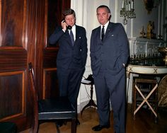 President Kennedy takes a phone call while Vice President Johnson tries to snoop on the conversation.