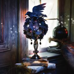 DIY Halloween Centerpiece - This dark and gloomy centerpiece is sure to attract the attention of your ghastly guests. A styrofoam ball is mounted atop a painted candle stick. Faux flowers are pushed into the ball, and a raven is perched upon it. Fantastic!