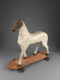 Pull horse with cast iron head. Raised on a platform base and original wheels. Carved block construction, painted wood and cast iron, Continental, c.1870.