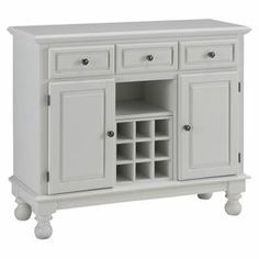 """Buffet with turned feet and wine storage.  Product: BuffetConstruction Material: WoodColor: WhiteFeatures:  Two door storage area with two adjustable shelvesThree drawersBun feetShelves can be used for display or wine storage Dimensions: 36"""" H x 43.75"""" W x 17"""" D"""