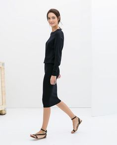Black midi dress with pencil skirt bottom and casual sandals.