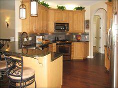 honey oak cabinets with dark hardwood floor | Birch cabinetry and black ubatuba granite countertops make the kitchen ...