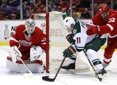 Minnesota Wild left wing Zach Parise (11) tries to score against Detroit Red Wings goalie Jimmy Howard (35) and defenseman Jonathan Ericsson (52) during the third period at Joe Louis Arena. The Red Wings won 3-2.  #9223443
