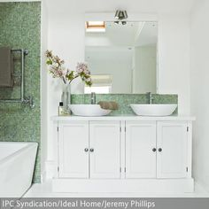 In diesem geräumigen Badezimmer finden gleich zwei Leute an den beiden Waschbecken Platz. Das Mosaik sorgt für farbige Akzente.