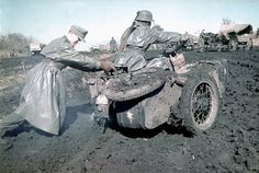 A Wehrmacht soldier assists his comrade in getting his motorcycle unstuck from the thick Ukrainian mud so he may continue forth to the Front. The Ukraine, Soviet Union. Spring, 1942.