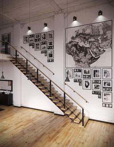mur de brique blanche, décoré de photos en noir et blanc, appliques murales orientables et escalier en bois et métal