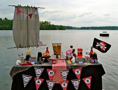 Pirates by the Lake (www.andersruff.com Aug 9, 2011) Table covered with a black table cloth & topped it with netting from the dollar store. A big sail was created using fabric that matched  the printables