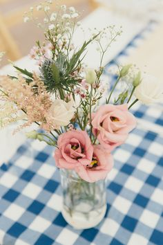 Lovely rustic style simple table centre piece using roses, wild flowers and a jam jar.  From real wedding feature 'A Floral Crown And Backless Gown For An Enchanting Woodland Wedding', by http://rebeccagoddardphotography.com/