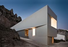 On the cliffs of Ayora, Spain, the stark white House on the Castle Mountainside is austere and bold in it's surroundings.