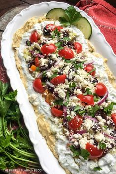 This Mediterranean Layer Dip is full of amazing flavor including hummus, feta, fresh tomatoes, and cucumbers. Layer dips are a great way to marry together a variety of flavors and they work wonderfully for any occasion. This is a perfect Summer party dip! #MediterraneanLayerDip #LayerDips #Recipes #Dips ThePurplePumpkinBlog #SummerRecipes #PartyFood