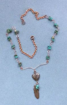 This necklace is a collection of wire wrapped turquoise chips, solid copper round curb link chain, and a hammered wire center piece with a copper heart and copper feather drop. The overall length is 17. The clasp is a copper magnetic clasp. The drop on the center piece is about 2.