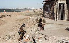Crianças brincam em praia no Pirambu. Ao fundo, pichação do Comando Vermelho.  Facções dominam periferias de uma das capitais mais violentas do Brasil e proíbem ciclo de vingança das gangues locais