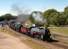 An excursion steam passenger train huffs and puffs into La Crosse, Wisconsin, USA, with Canadian Pacific Engine 2816 leading the way in front of Milwaukee Road Engine 261.