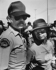 The photograph shows author Alice Walker being arrested and taken into custody during a protest in Concord, California in the 1980s, against weapons shipments being sent to Central and South America. Learn more at: http://www.openroadmedia.com/authors/alice-walker.aspx