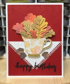 Leaves and Acorns: Botanicuts: Mighty Oak from the Greetery; Teacup: Tea Party by The Ton; Sentiment: Doodle Happy Birthday by Poppystamps; Tablecloth: Cozy Cup Coaster by the Greetery; Background stamp: Floral Spray Cover-a-Card by Impression Obsession @thegreetery @thetonstamps @poppystamps @iostamps #fallwinter2020clh
