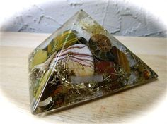 This is a gorgeous orgone generator pyramid! This orgone pyramid was made with a Botwswana agates, clear quartz, sunstone, ocean agate, ammonite, tiger eye, selenite, red jasper, fossil shark teeth, steel, brass, zinc and copper. It is such a pretty orgone.    The basic and simplified theory of how the orgone devices work is that the negative energy is attracted into the device by the organic component and then it gets bounced back and forth between the resin and suspended metal particles…
