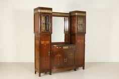 Fronte mosso, presenta due corpi laterali con vetri bisellati. Specchio centrale. Intarsi e fregi in bronzo.