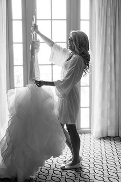 """If your photographer is scheduled to arrive in the early hours before the ceremony, then you'll want to take some photos interacting with the dress. This bride's ecstatic expression gives us all the feels.Related: 60 Must-Have """"Getting Ready"""" Photos"""