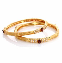 hand-crafted 22 carat gold bangles with single stone covered in white stones
