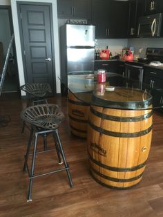 Re-purposed authentic Jack Daniels Whiskey barrel table bar. Autograph can be seen. Cut 1/2 inch tempered glass in racetrack design with rounded edges topped off with tractor seat adjustable stools.