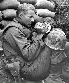 El sargento Frank Praytor alimenta a un gatito después de que la madre fue asesinada por fuego de mortero. [Guerra de Corea de 1953].
