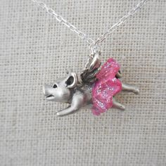 Quit porkin around and get this Piggy! This pendant represents the idea that the impossible is attainable. This little piggy is Sterling. This little piggy is cute. This little piggy is perfect. Most little piggies are not. But this little piggy the tiniest little piggy can fly all the way to your door! This little pig was hand-carved in wax and cast in Sterling Silver. It is solid and is 3 dimensional. The tutu is painted pink sprinkled with glitter and has resin added to protect it. The…
