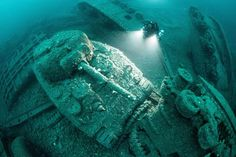 A diver swims over wrecked WWII tanks littering the seabed