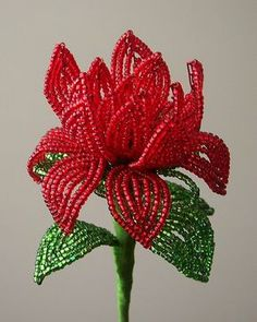 """French beaded red forest fire dahlia. Height: approximately 10"""" These flowers were made using the French beading technique. Tiny seed beads are strung onto flexible wire and shaped into various flower components. These parts are then crafted to make a flower and then tape and embroidery floss are wrapped around the stem to give them a finished and professional appearance. Contact me at ayanacreations@gmail.com for purchasing information"""