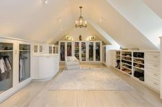 A very gorgeous attic walk-in closet, going for a bright and feminine look by using light colors. Walls and the sloped ceiling were all painted white, and the floors is engineered wood in a very light beech wood color, adding a subtle touch of warm color in the space. For the cabinets, white is the color of choice as well, whit closed cabinet doors fixed with glass panels.