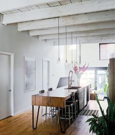 SPLIT THE DIFFERENCE Nicolas Gervais designed the pendant lights above the Plasse designed and Stéphane Bilodeau built kitchen island in this century-old Montreal house. The combination of the woodwork and exposed beams with modern lines, hardware and accessories makes this kitchen a great example of rustic modern done right.
