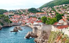 Walking the city walls in Dubrovnik, Croatia – the city from above, with dramatic cliffs, red-roofed buildings and ancient gates and towers.