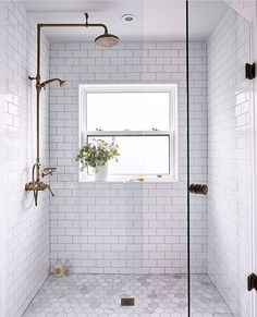 Clean white tiles give this bathroom a modern feel, but the shower head brings in a rustic element. The light here is beautiful as well and that big glass door keeps the room bright and open.